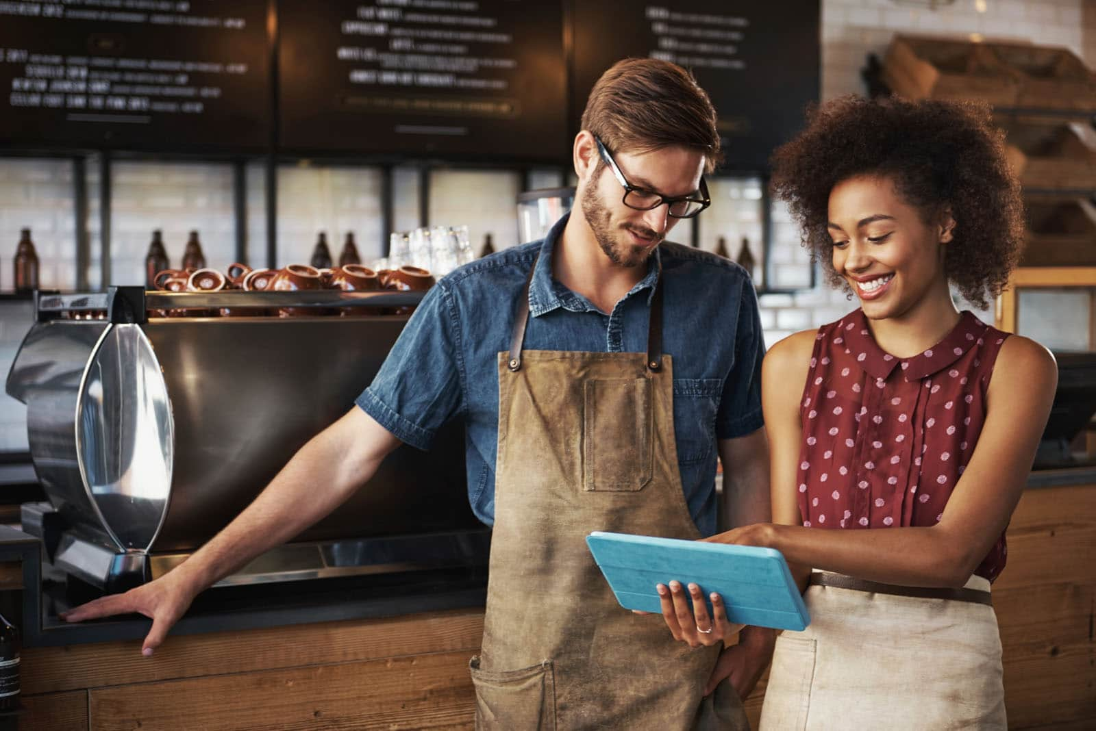 Shot of a smiling woman and man standing inside a coffee shop looking at something on their touchscreen